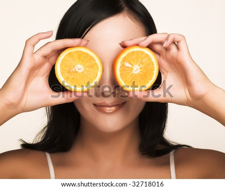 beautiful cheerful woman with fresh orange near her face - stock photo