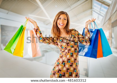 Beautiful cheerful woman with many multi colored shopping bags in the shopping mall.