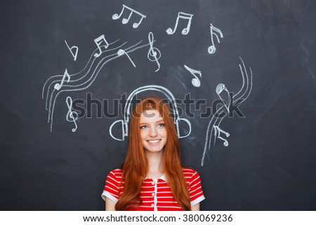 Beautiful cheerful young woman listening to music in earphones  drawn on chalkboard background - stock photo