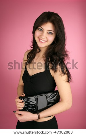 Beautiful cheerful young woman with handbag over pink background - stock photo