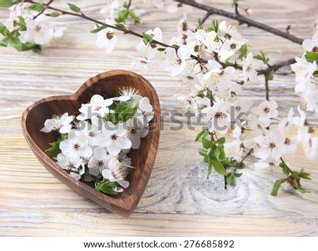 beautiful cherry blossoms in a vase in the form of heart on the wooden background