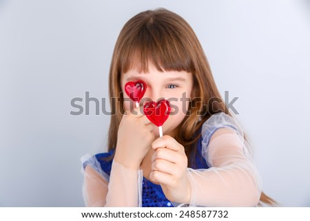 Beautiful child girl  holding a lollipop in the shape of a red heart valentines day - stock photo