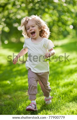 Beautiful child goes in for sports in the summer. Green nature background - stock photo