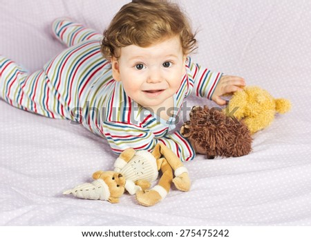 Beautiful child in crib with toys. Cute boy. Curly blonde. Portrait of a baby