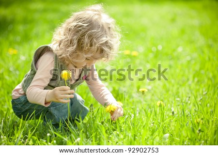 Beautiful child picks flowers on a spring green meadow - stock photo