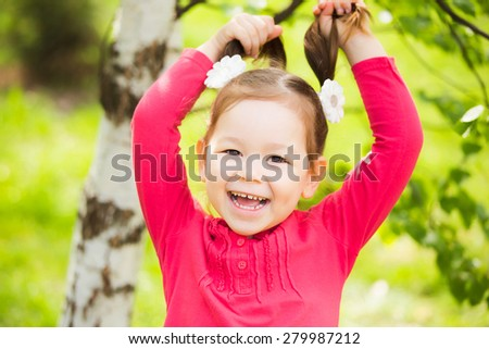 Beautiful child playing with her hair outside. Carefree cheerful baby. closeup portrait of funny little kid. beautiful girls face happy laughing - stock photo