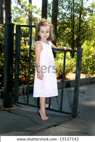 Beautiful child poses besides garden gate.  Black iron gate fronts sunshine and trees. - stock photo