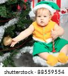 Beautiful child sitting with presents against Christmas background. - stock photo