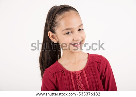 Beautiful child smiling in red dress on white background