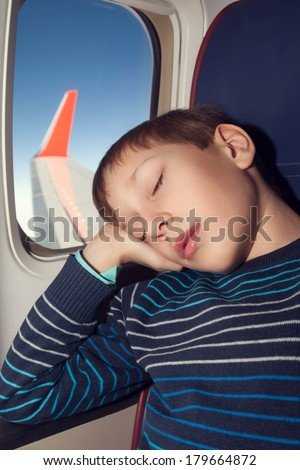 Beautiful child traveling by airplane sleeping in a seat near a window - stock photo