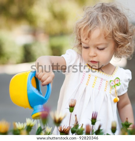 Beautiful child watering spring flowers against green natural background - stock photo