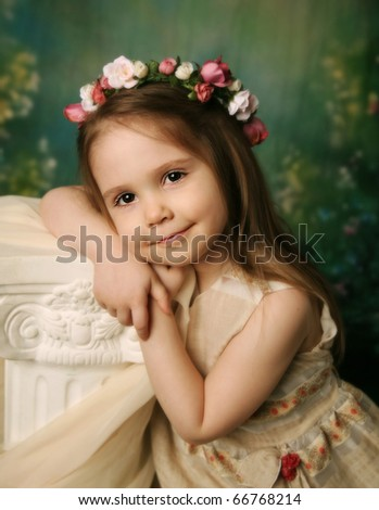 Beautiful child wearing a flower wreath halo leaning on a cream pedestal, with a serene expression on her face - stock photo