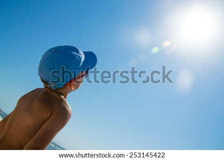 Beautiful child wearing colorful sunglasses looking on sun - stock photo