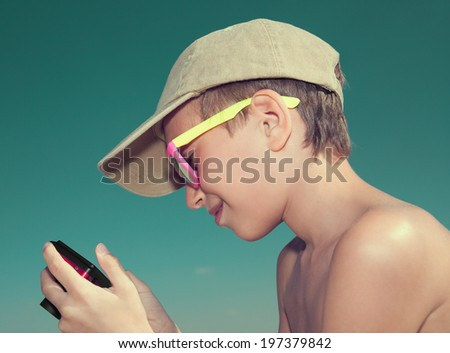 Beautiful child wearing stylish sunglasses and cap on a sandy beach holding a camera  - stock photo