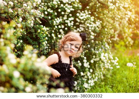beautiful child with a crown and blooming bush