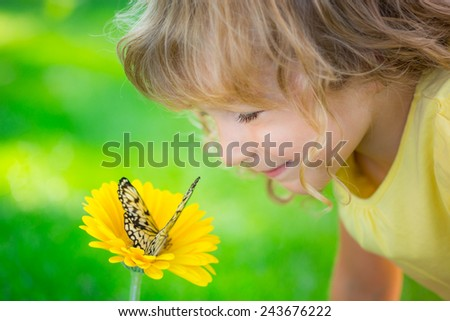 Beautiful child with butterfly in spring park. Happy kid playing outdoors - stock photo