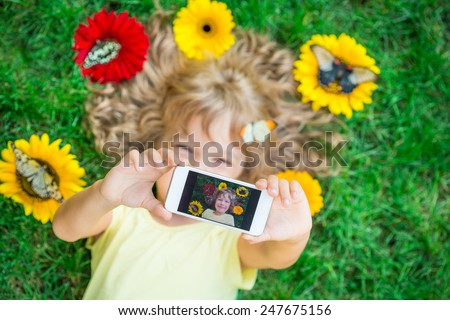 Beautiful child with butterfly in spring park. Happy kid taking selfie outdoors. Unusual top view portrait - stock photo