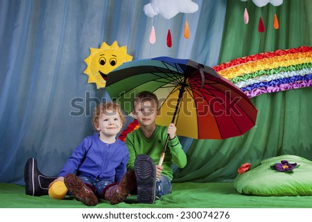 Beautiful children brother and sister on the bright lawn under an umbrella on a background of a rainbow and the sun with clouds - stock photo