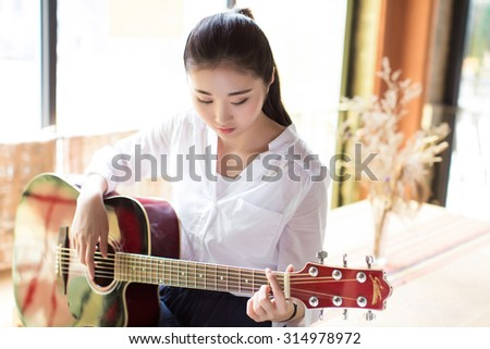 beautiful chinese black hair girl �¯�¼? playing acoustic guitar over indoor