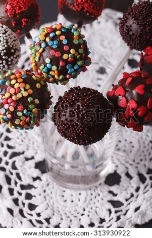 Beautiful chocolate cake pops with candy sprinkles close-up on the table. vertical top view - stock photo