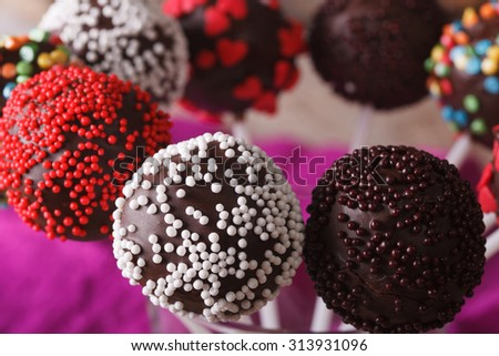 Beautiful chocolate cake pops with multicolored candy sprinkles macro. horizontal