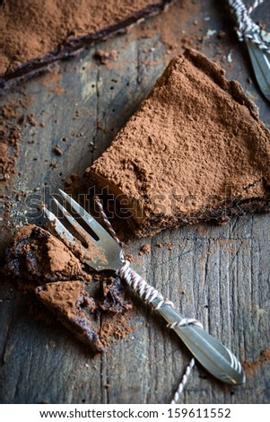 Beautiful chocolate tart sliced into pieces with small forks to serve - stock photo