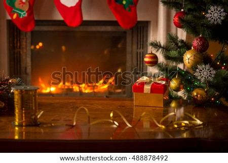 Beautiful Christmas background with burning fireplace, Christmas tree, gift box and wooden table