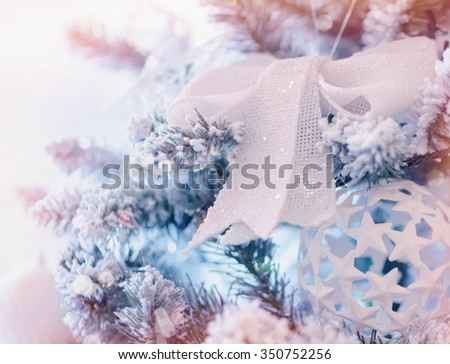 Beautiful Christmas decoration, beautiful white bow and ball made by many little stars hanging on festive fir tree, happy winter holidays - stock photo