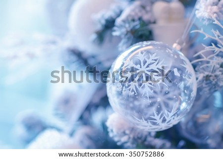 Beautiful Christmas decoration, transparent ball with snowflake decoration hanging on festive fir tree, happy winter holidays - stock photo