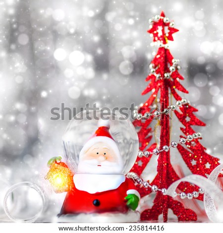 Beautiful Christmas still life, cute Santa Claus toy with little decorative red christmas tree on silver blurry background, beauty of winter holidays concept - stock photo