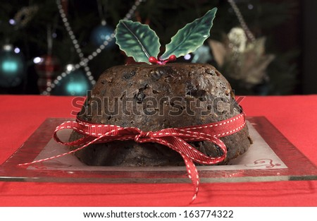 Beautiful Christmas table setting in front of Christmas Tree, featuring a classic plum pudding with holly on red tablecloth. - stock photo