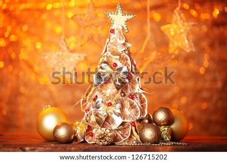 beautiful christmas tree of dry lemons with decor, on orange background - stock photo
