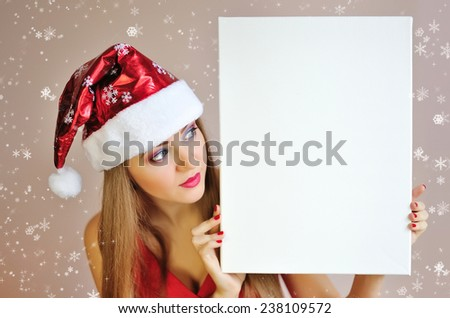 Beautiful christmas woman in santa hat with blank white board - stock photo