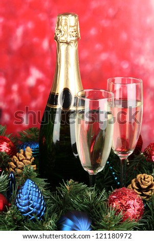 Beautiful Christmas wreath in composition with champagne on red background - stock photo