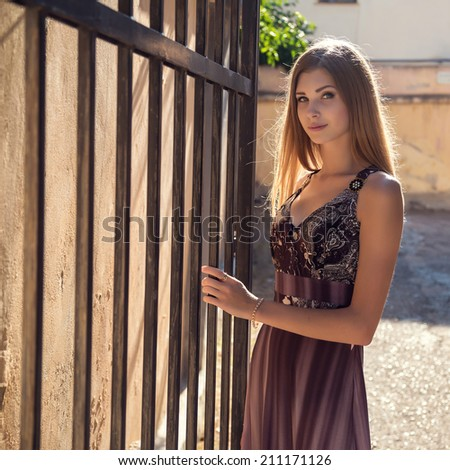 Beautiful city woman has walking on a street. The girl in the sunset