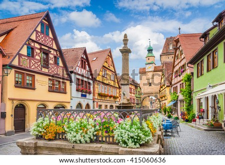 Beautiful classic postcard view of the famous historic town of Rothenburg ob der Tauber on a sunny day with blue sky and clouds in summer, Franconia, Bavaria, Germany - stock photo