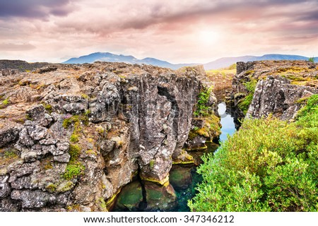 Beautiful cliffs and deep fissure in Thingvellir National Park. Southern Iceland - stock photo