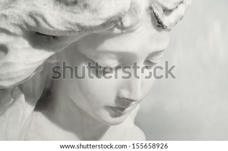 Beautiful close up af a face angel marble sculpture with a sweet expression that looks down - stock photo