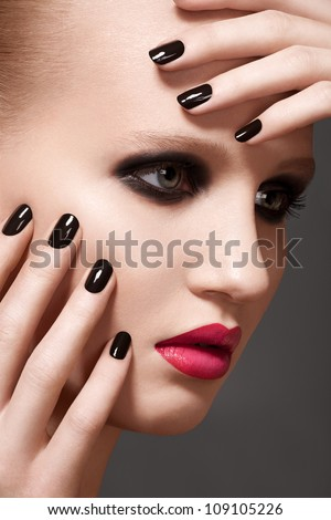 Beautiful close-up portrait of fashion woman model with glamour bright makeup, dark magenta lipstick, black nail polish. Evening catwalk style, trend visage and manicure