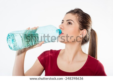 Beautiful close-up portrait of young woman drinking water from the bottle. Healthy drink and sport concept. Skin care and beauty. Sports. - stock photo