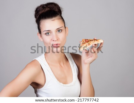 Beautiful close-up portrait of young woman eating pizza. Healthy and junk food concept. Skin care and beauty. Diet.