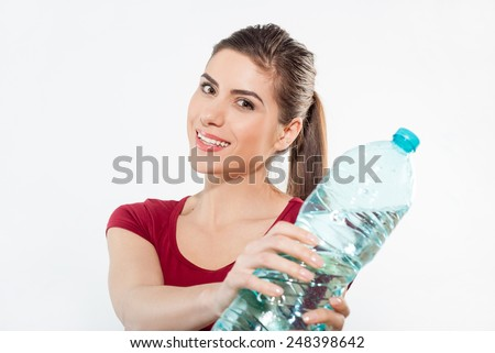 Beautiful close-up portrait of young woman with a bottle of water. Healthy drink and sport concept. Skin care and beauty. Sports. - stock photo