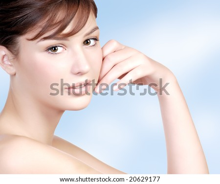 Beautiful close-up teen face on the blue background - stock photo