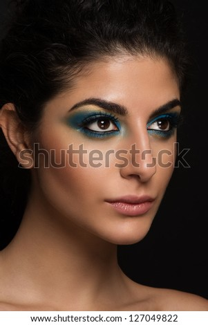 Beautiful closeup portrait of young caucasian female on black background. Dark blue and yellow makeup, natural lips, perfect skin. Big brown eyes with long eyelashes. - stock photo