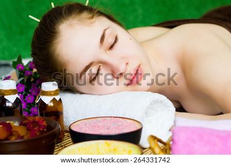 Beautiful closeup woman with closed eyes at a spa salon - stock photo