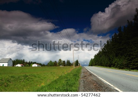 Beautiful clouds over a country road in early summer - stock photo