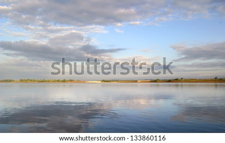 Beautiful clouds over the broad river, reflected in the water - stock photo