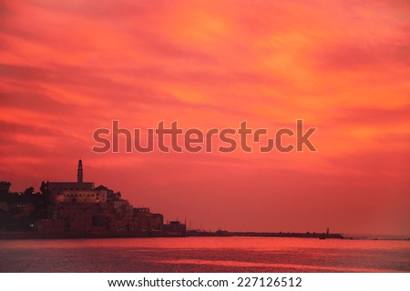 Beautiful cloudscape over the sea after sunset and view on Old Jaffa (Jaffa, Tel-Aviv, Israel). Toned photo. - stock photo