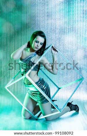 beautiful club girl with metal cube posing on silver background - stock photo