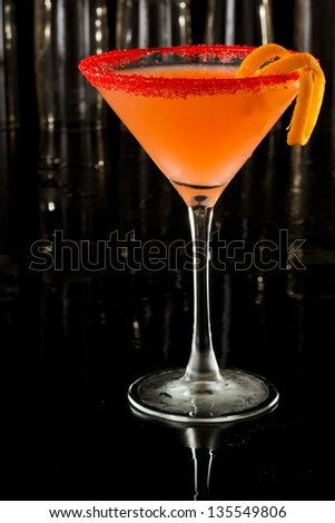 beautiful cocktail served on a dark bar garnished with an orange twist and a sugar rim